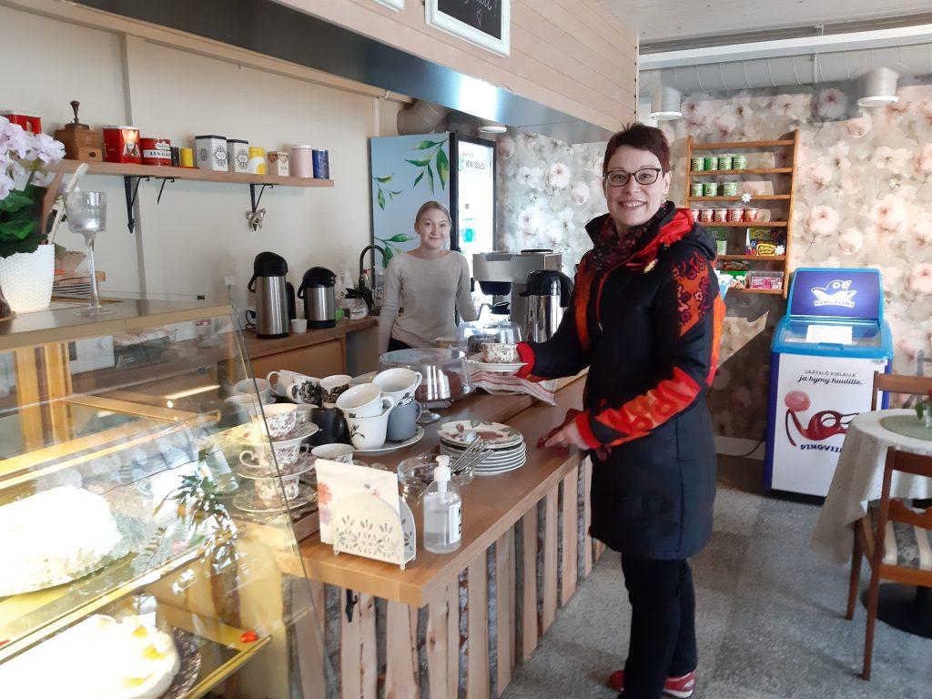 Osulan kahvilassa asiakas ottaa kahvia ja nuori myyjä palvelee.