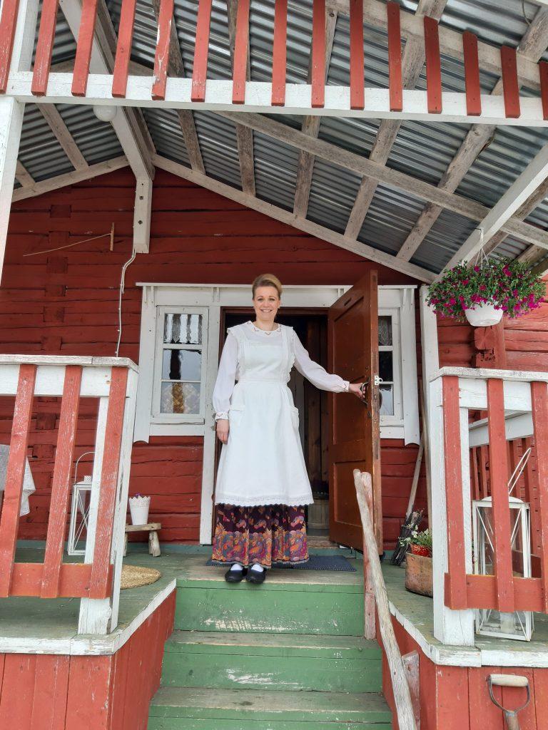 Mervi Rönkä seisoo Kalapuro-tilan talon ovella ja toivottaa tervetulleeksi.