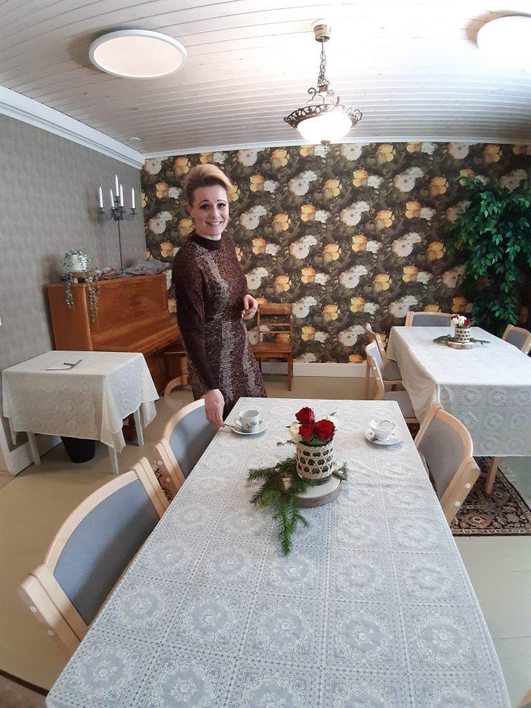 Yrittäjä Mervi Rönkä kattaa kahvipöytää juhlasalissa ja hymyilee.