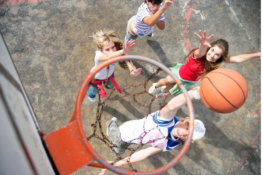 Tytöt ja pojat pelaavat koripalloa kentällä