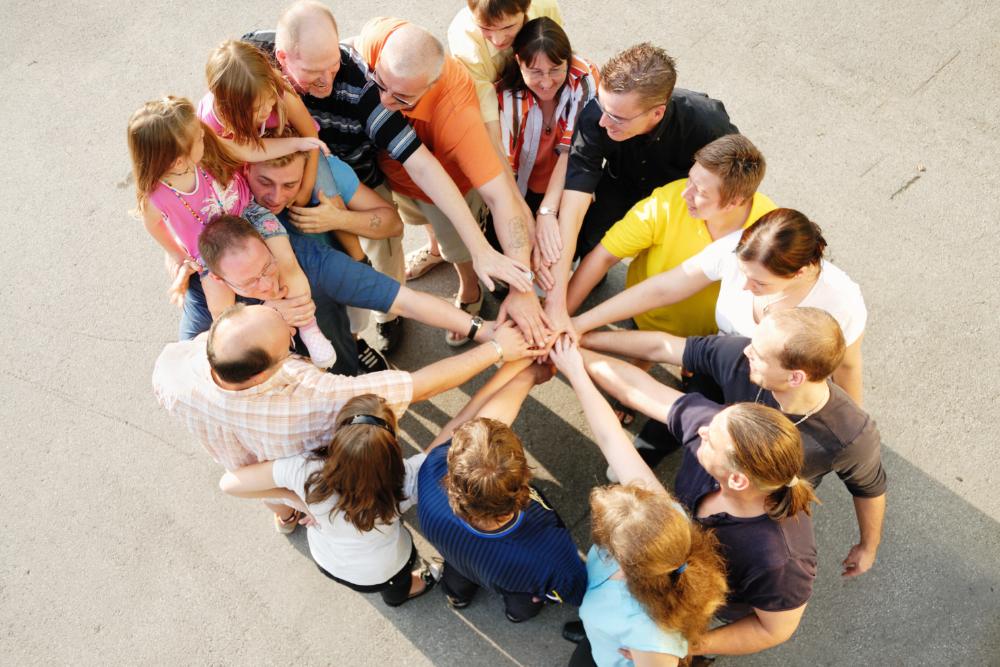 Eri-ikäiset ihmiset seisovat ympyrässä kädet yhdessä ja kannustavat toisiaan