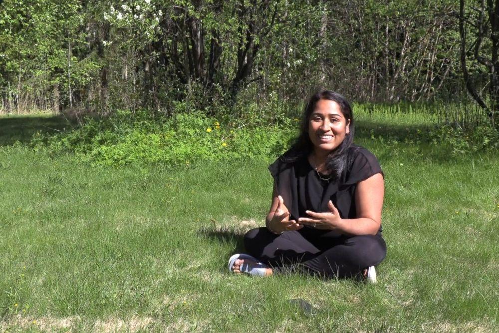 Yrittäjä Parvathy Venugopal istuu ruohikolla ja hymyilee.