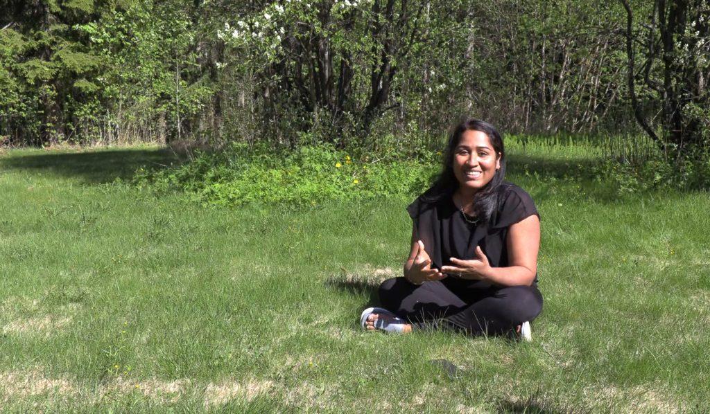 Parvathy Venugopal istuu ruohikolla ja kertoo yritystoiminnastaan.