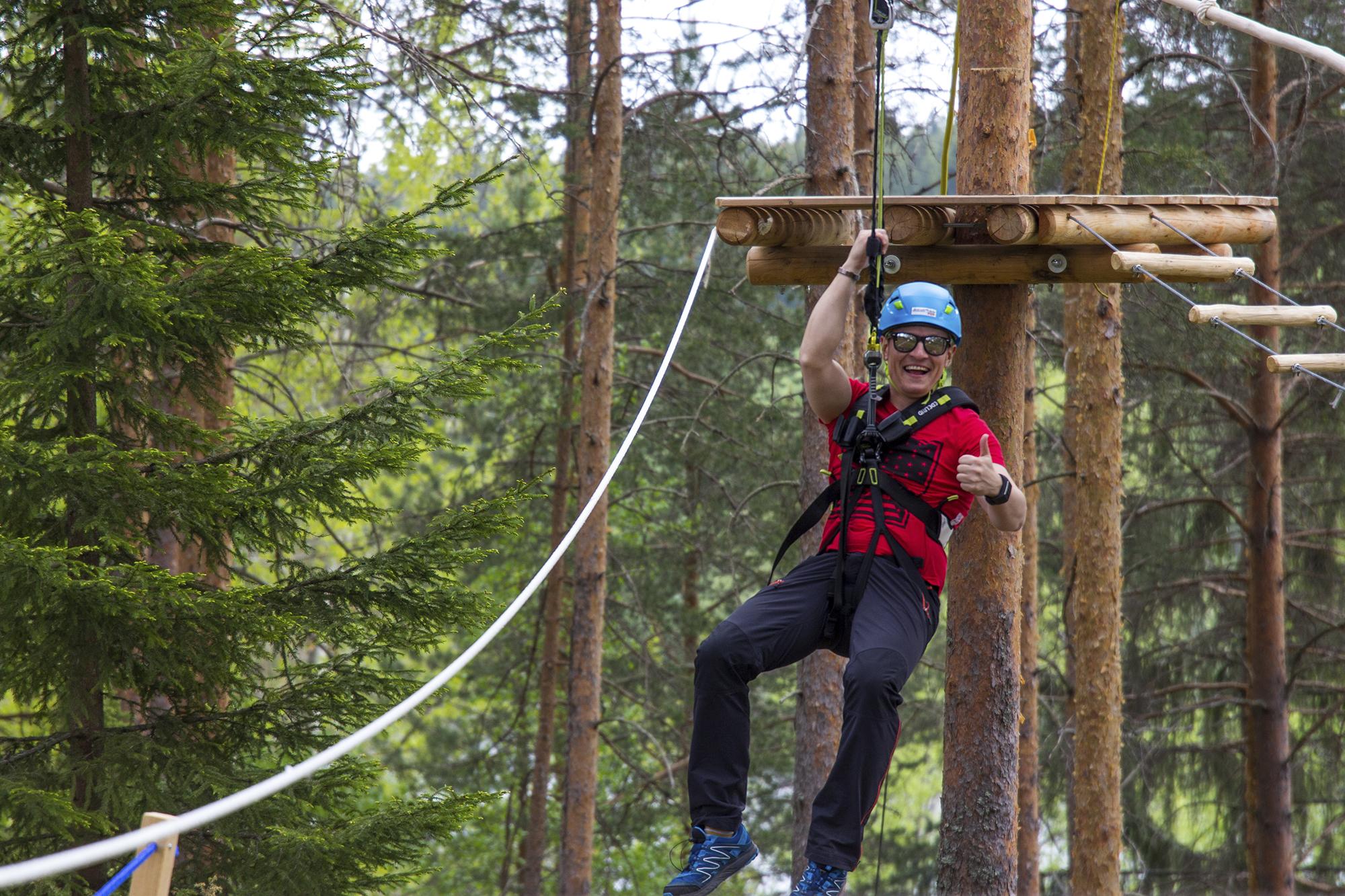 Mies roikkuu valjaissa Seikkailupuisto Leppiksen köysiradalla, hymyilee ja näyttää peukkua. Puisto on yksi rahoitusta saaneista kohteista.