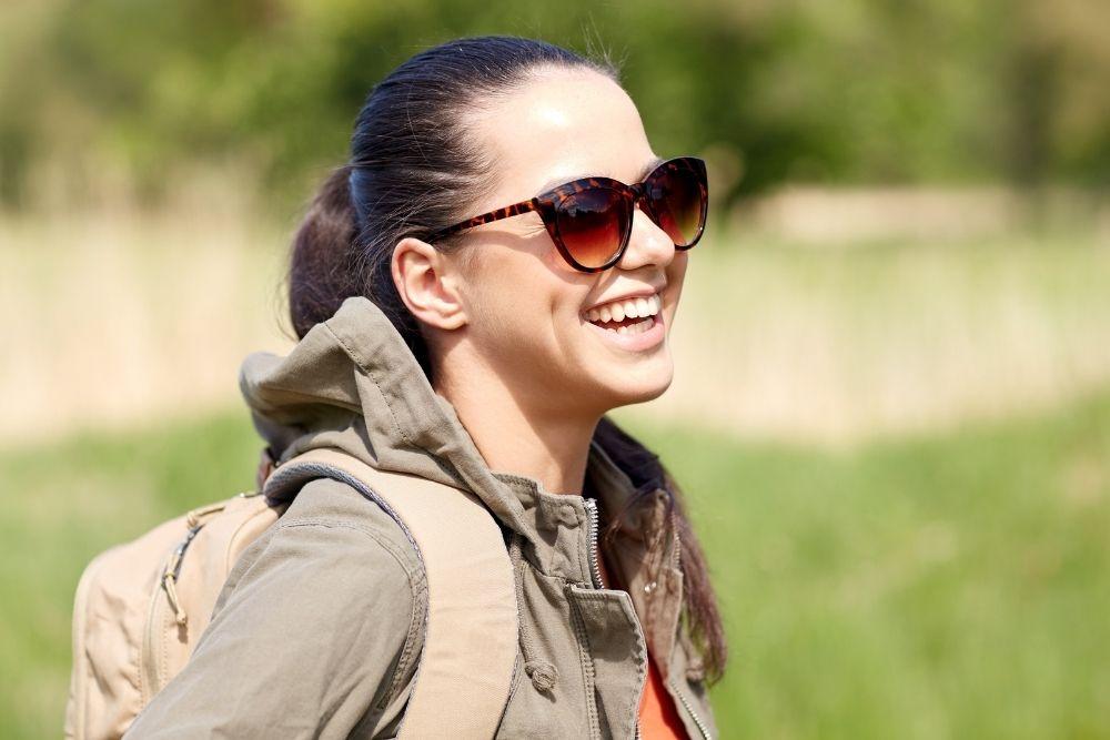 Tytöllä on aurinkolasit, reppu selässä ja hän hymyilee