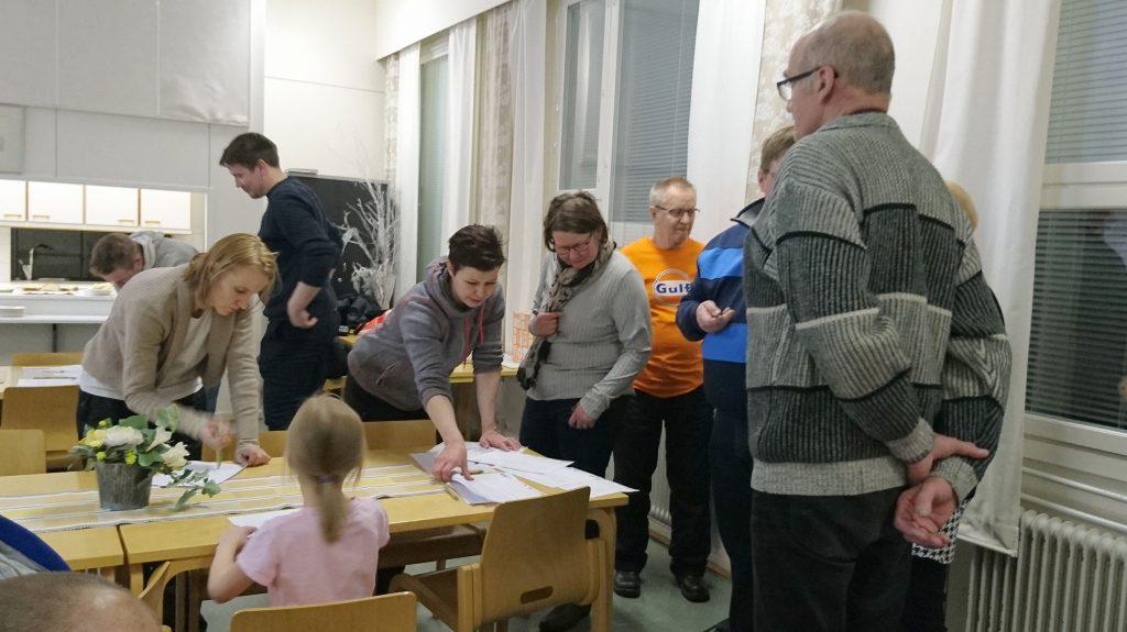 Eri-ikäiswet ihmiset ovat kokoontuneet suunittelemaan palvelujan yhdessä työpöydän äärelle.